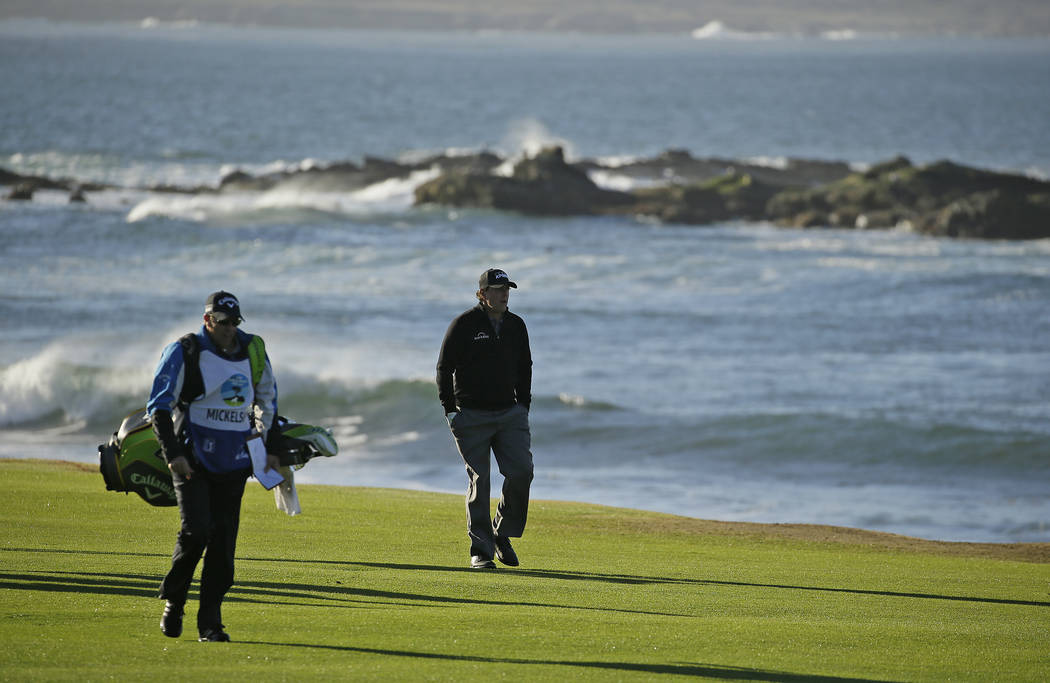 Phil Mickelson walks up the 18th fairway of the Pebble Beach Golf Links with his brother and caddie Tim Mickelson during the final round of the AT&T Pebble Beach Pro-Am golf tournament Monday, ...