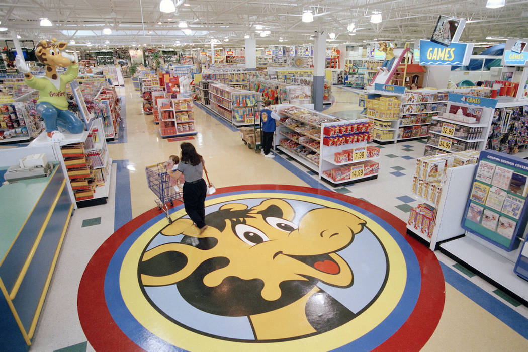 In this July 30, 1996, file photo, a woman pushes a shopping cart over a graphic of Toys R Us mascot Geoffrey the giraffe at the Toys R Us store in Raritan, N.J. (AP Photo/Daniel Hulshizer, File)