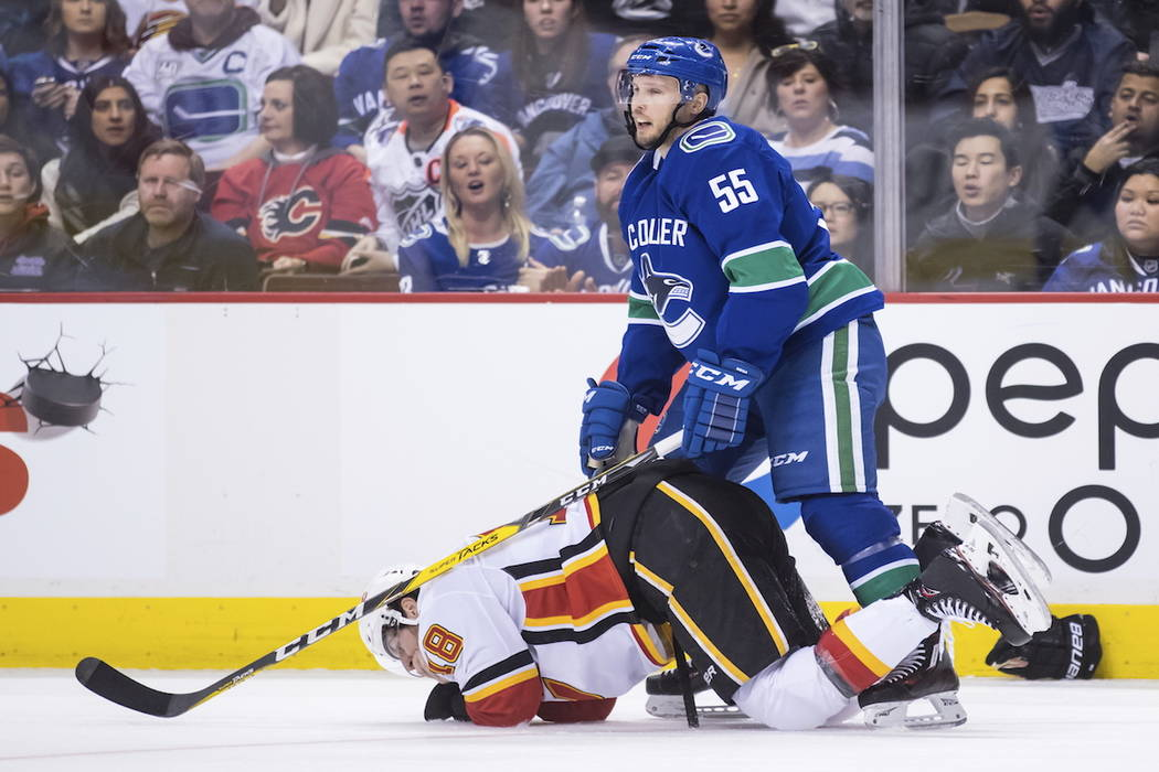 Calgary Flames' James Neal, bottom, holds his mouth after taking a high stick to the face from Vancouver Canucks' Alex Biega (55) and losing teeth during the third period of an NHL hockey game Sat ...