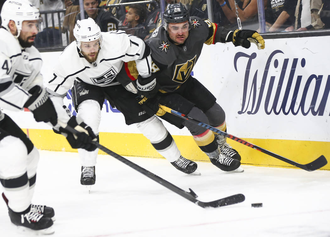 Golden Knights left wing William Carrier (28) and Los Angeles Kings defenseman Oscar Fantenberg (7) chase after the puck during the first period of an NHL hockey game at T-Mobile Arena in Las Vega ...