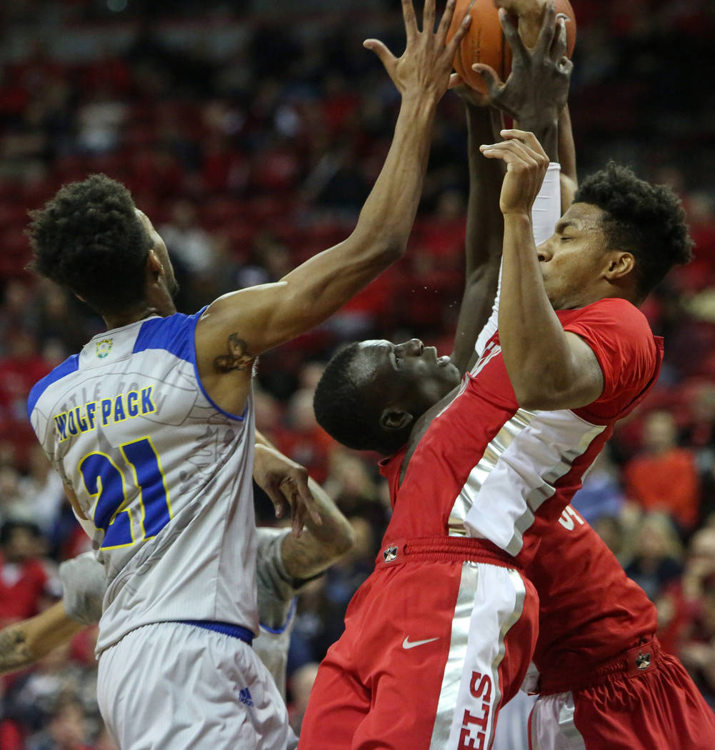 Nevada Wolf Pack forward Jordan Brown (21) UNLV Rebels forward Cheikh Mbacke Diong (34) and UNLV Rebels forward Nick Blair (20) battle for the ball during the second half of a basketball game at t ...
