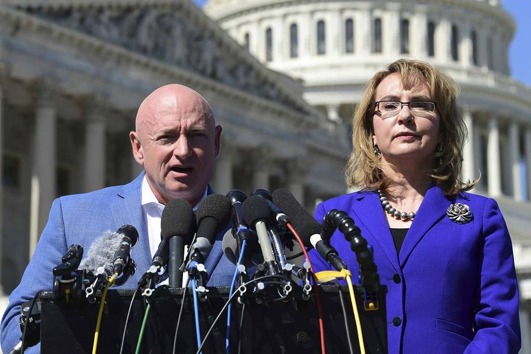 In this Oct. 2, 2017, file photo former Rep. Gabrielle Giffords, D-Ariz., right, listens as her husband Mark Kelly, left, speaks on Capitol Hill in Washington. Kelly said Tuesday, Feb. 12, 2019, t ...