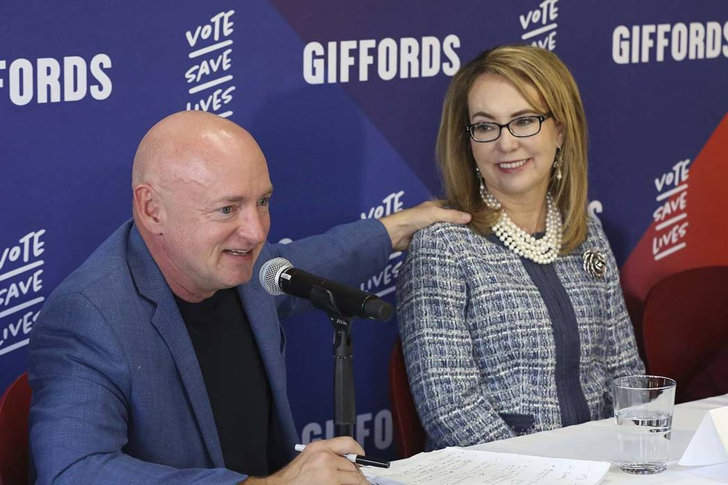 In this Oct. 2, 2018, file photo retired NASA astronaut and Navy Capt. Mark Kelly speaks as his wife, former U.S. Rep. Gabby Giffords looks on during a roundtable discussion with gun violence surv ...