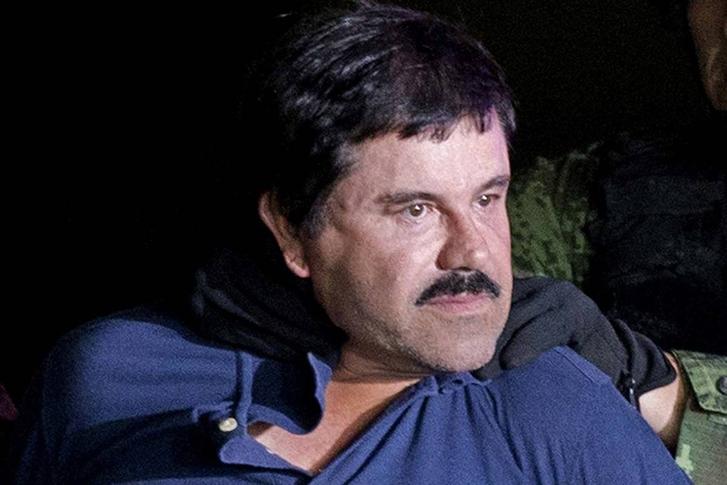 """In this Jan. 8, 2016 file photo, drug lord Joaquin """"El Chapo"""" Guzman is made to face the media in Mexico City as he is escorted by Mexican soldiers following his recapture six months after escapin ..."""