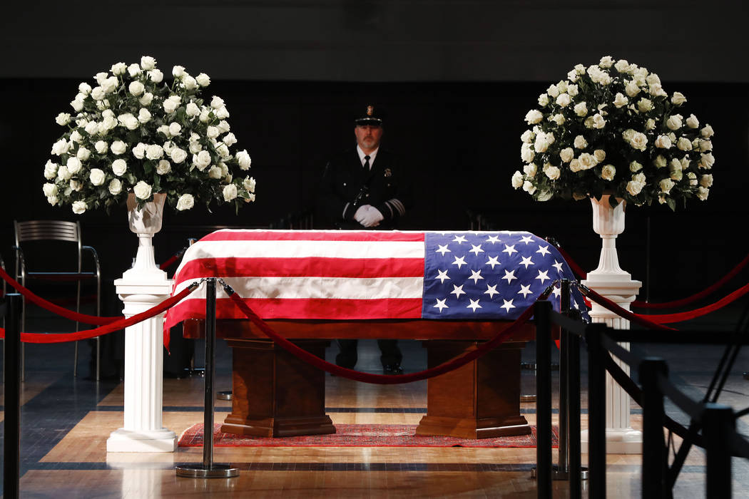 A police officer stands guard stands guard at the casket of former Michigan Rep. John Dingell, lying in repose in Dearborn, Mich., Monday, Feb. 11, 2019. Dingell, the longest-serving member of Con ...