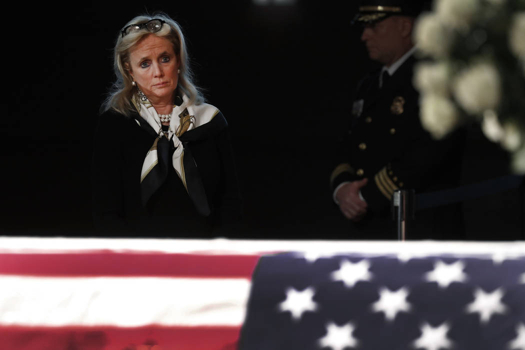 Rep. Debbie Dingell, D-Mich., stands at the casket of her husband and former Rep. John Dingell, lying in repose in Dearborn, Mich., Monday, Feb. 11, 2019. John Dingell, the longest-serving member ...
