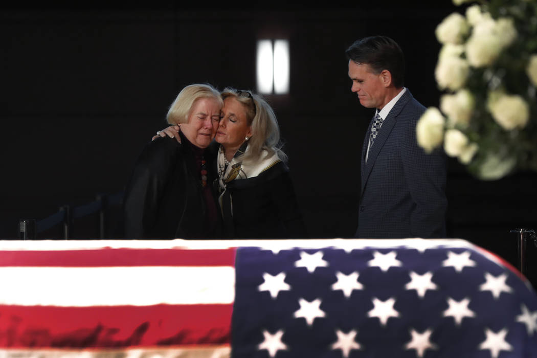 Rep. Debbie Dingell, D-Mich., center, consoles former Rep. Candice Miller, R-Mich., as Macomb County executive Mark Hackel, right, looks on at the casket of her husband and former Rep. John Dingel ...