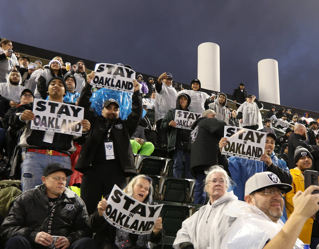 Fans hold up signs at the Oakland-Alameda County Coliseum before the start of an NFL game between the Oakland Raiders the Denver Broncos in Oakland, Calif., Monday, Dec. 24, 2018. Heidi Fang Las V ...