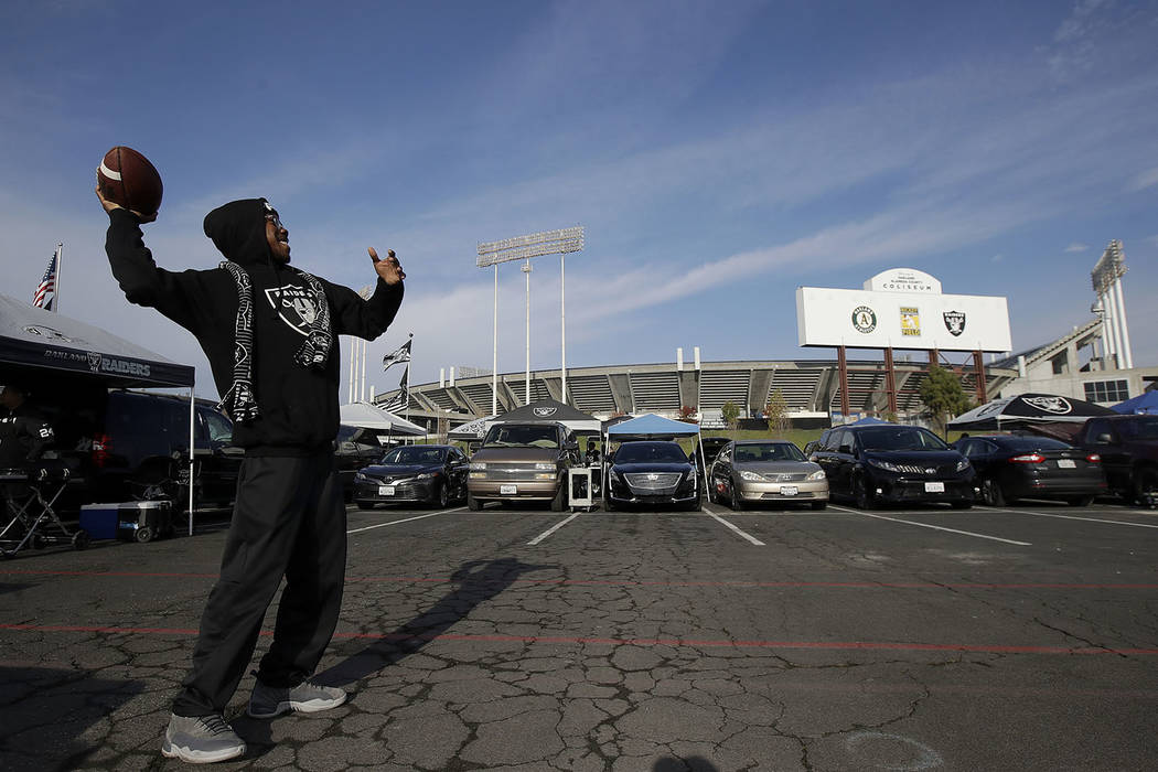 In this Dec. 9, 2018, file photo, a fan throws a football as people tailgate outside Oakland Coliseum before an NFL football game between the Oakland Raiders and the Pittsburgh Steelers in Oakland ...