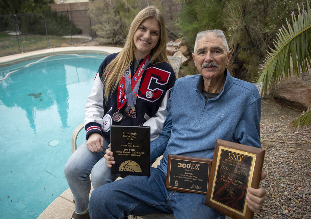 Sasha Bolla wears volleyball medals she has earned as she poses for a photograph with her father Jim Bolla, former UNlV women's basketball coach, as he holds plaques he has been awarded for his co ...