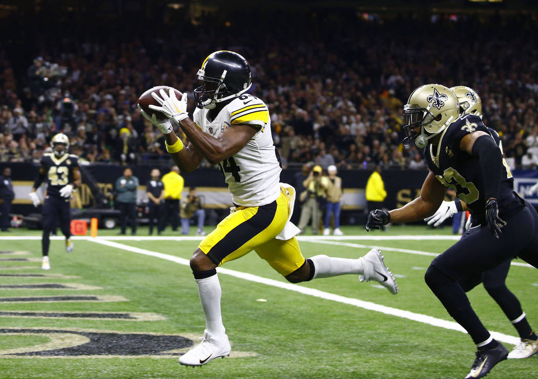 In this Dec. 23, 2018, file photo, Pittsburgh Steelers wide receiver Antonio Brown (84) pulls in a pass reception in front of New Orleans Saints cornerback Marshon Lattimore, foreground right, and ...