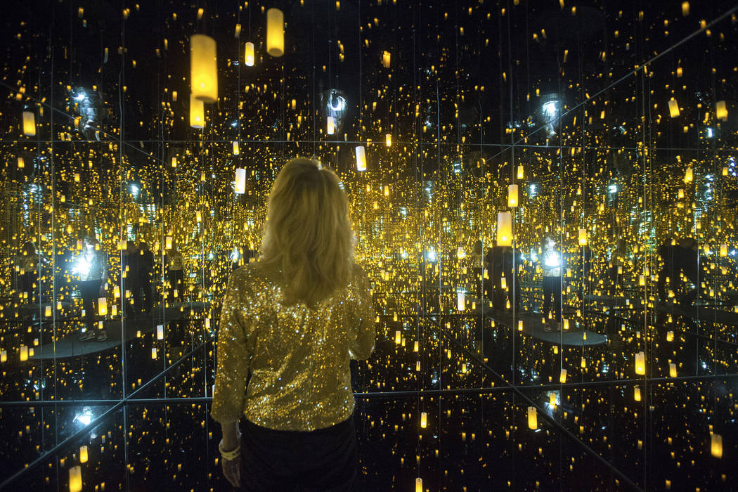 """Dawn Michelle Baude explores the """"Infinity Mirrored Room"""" at Yayoi Kusama's new exhibit at Bellagio Gallery of Fine Art on Friday, Nov. 16, 2018, in Las Vegas. Benjamin Hager Las Vegas ..."""