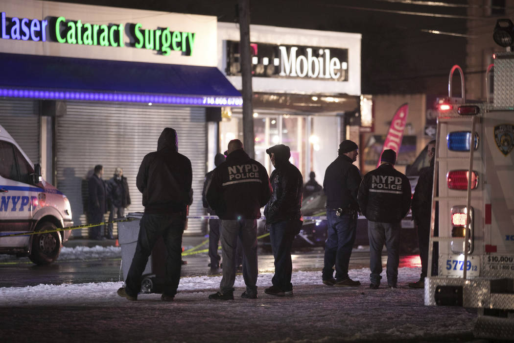 Investigators look over the area after a few New York City police officers were shot while responding to a robbery at a T-Mobile store in the Queens borough of New York on Tuesday, Feb. 12, 2019. ...