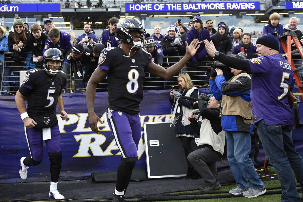In this Dec. 30, 2018, file photo, Baltimore Ravens quarterbacks Lamar Jackson (8) and Joe Flacco (5) run onto the field before an NFL football game against the Cleveland Browns, in Baltimore. (A ...