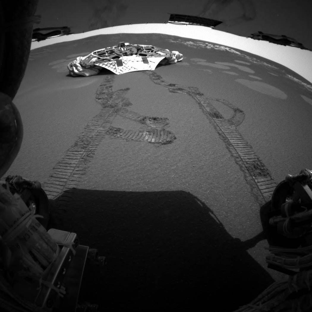This photo released Thursday, Feb. 5, 2004 made by one of the rear hazard-avoidance cameras on NASA's Opportunity rover, shows Opportunity's landing platform, with freshly made tracks leading away ...