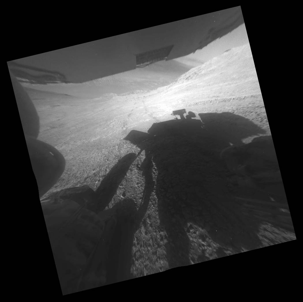 This March 22, 2016 photo made available by NASA shows the shadow and wheel tracks of the Mars Exploration Rover Opportunity just after a drive on a slope above Endeavour Crater. The image has bee ...