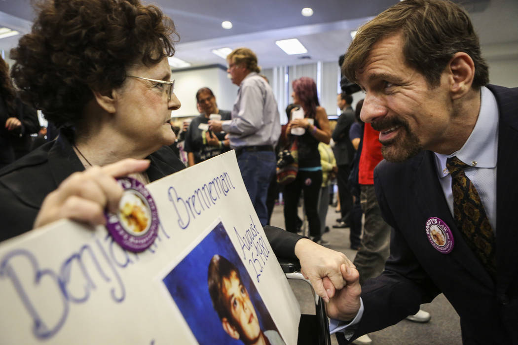 Henry Nicholas III speaks with the mother of a murder victim during a 2013 Orange County Victims' Rights March in Santa Ana, Calif. Nicholas is the chief architect of Marsy's Law, named for his si ...