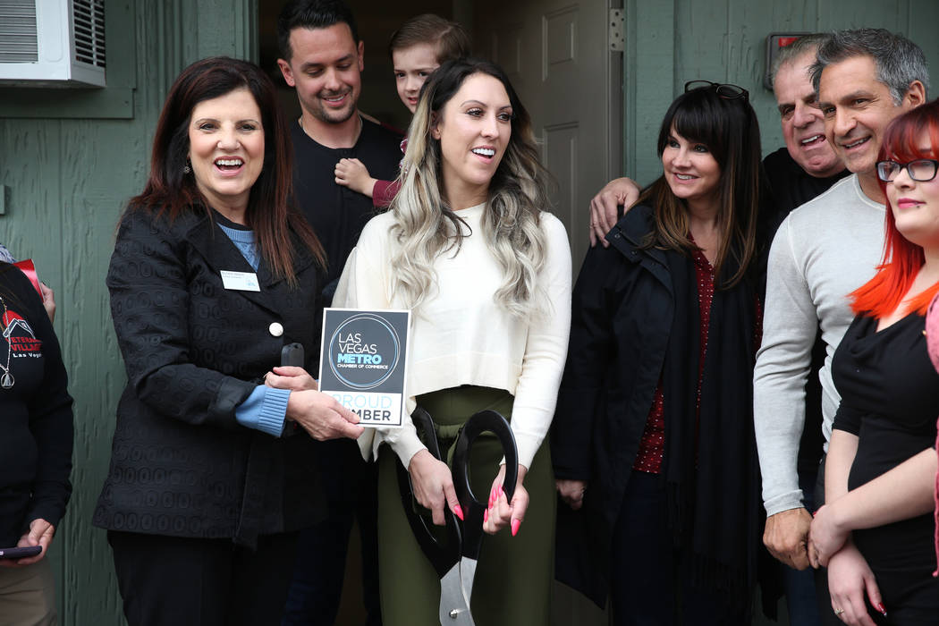 Michelle Weston, left, representative for the Las Vegas Metro Chamber of Commerce, presents Nicole Christie with a member plaque during the ribbon cutting ceremony of her new business T.H.E. Salon ...