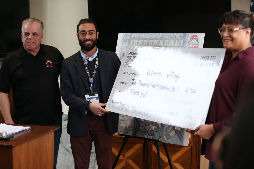 Arnold Stalk, from left, president of Veterans Village, is presented by a check by Ahmed Malha and Jo McDonald from Pisos dispensey, during an event at the Veterans Village in Las Vegas, Wednesday ...