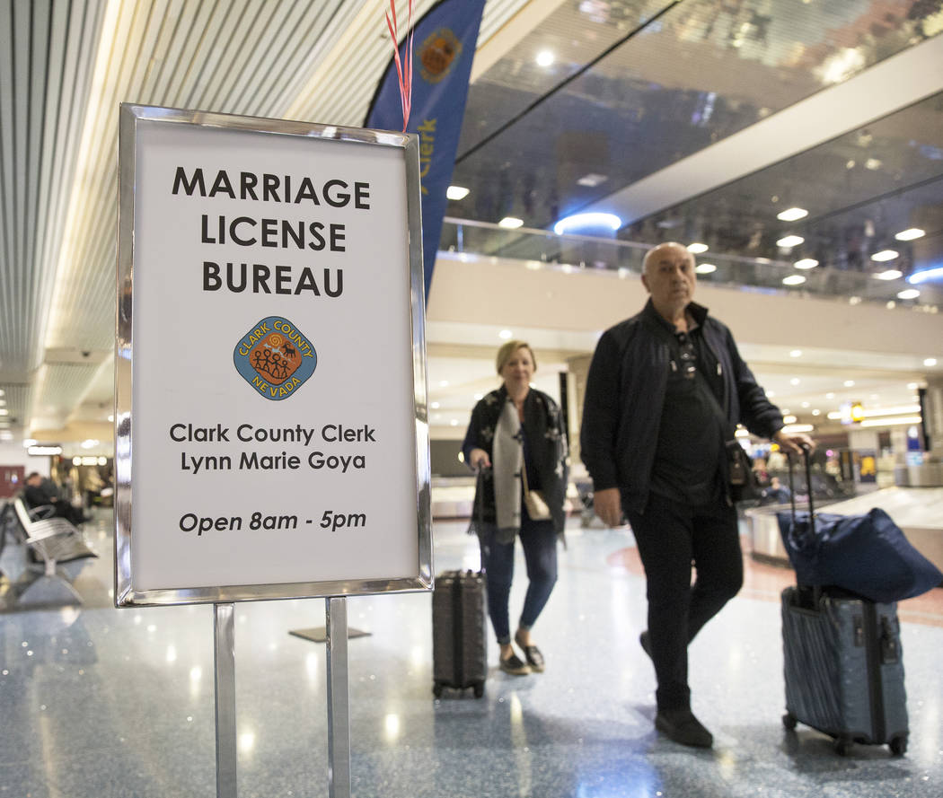 Travelers pass by a Clark County pop-up office offering marriage licenses in the baggage claim area in Terminal 1 on Wednesday, Feb. 13, 2019, at McCarran International Airport, in Las Vegas. (Ben ...