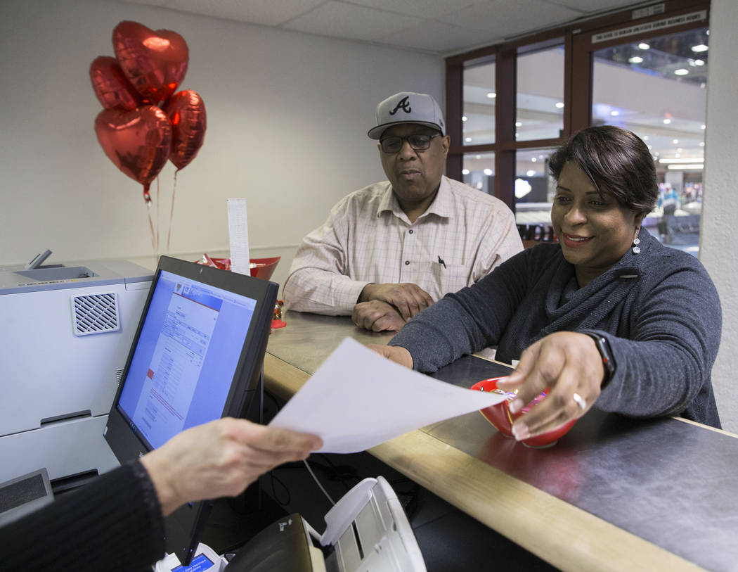 Tandra Jones, right, from Charleston, S.C., and husband Dennis fill out the paper work to get their marriage license at a Clark County pop-up office in the baggage claim area at Terminal 1 on Wedn ...