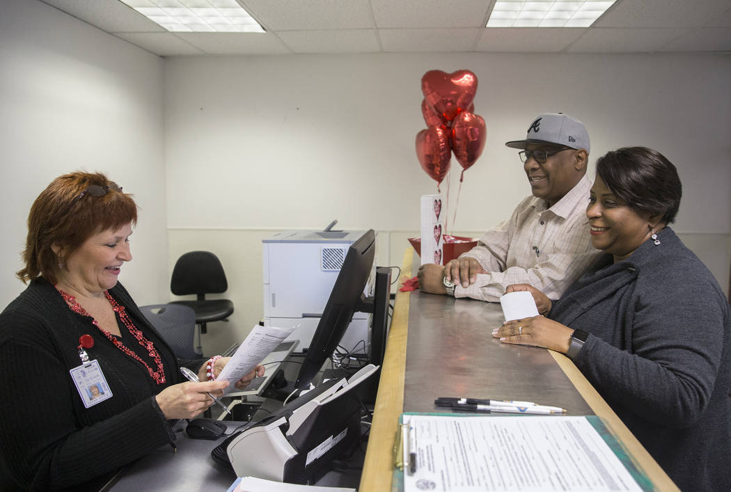 Paula Cook, left, a supervisor with the Clark County Marriage License Bureau, helps Tandra and Dennis Jones, from Charleston, S.C., get their marriage license at a Clark County pop-up office in th ...