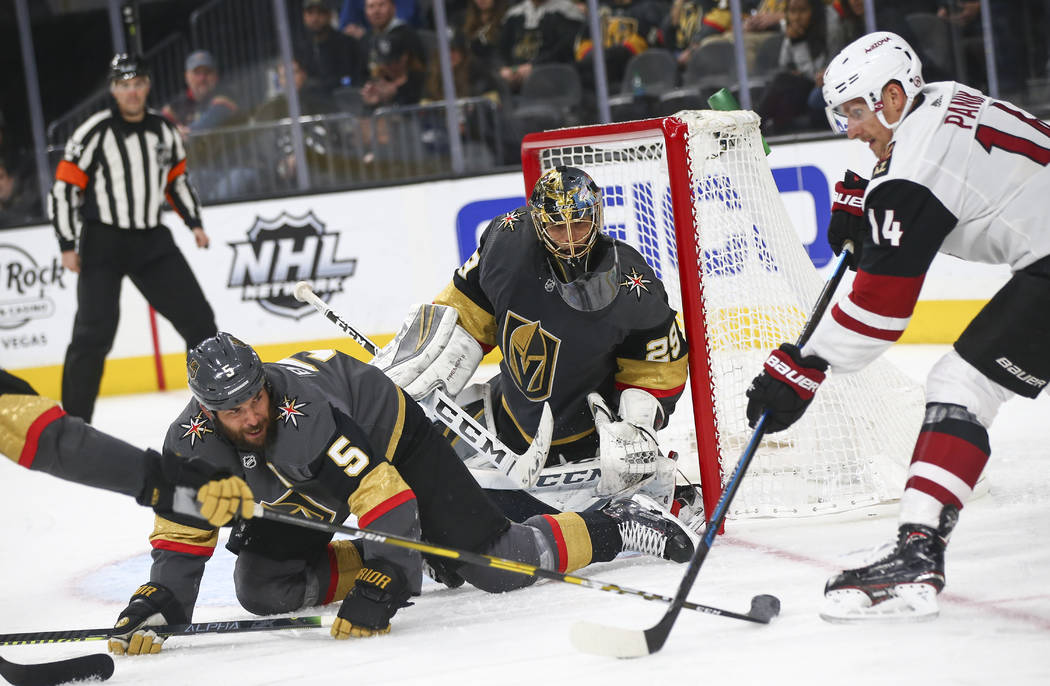 Golden Knights defenseman Deryk Engelland (5) gets tripped up in front of goaltender Marc-Andre Fleury (29) as Arizona Coyotes right wing Richard Panik (14) tries to shoot the puck during the thir ...