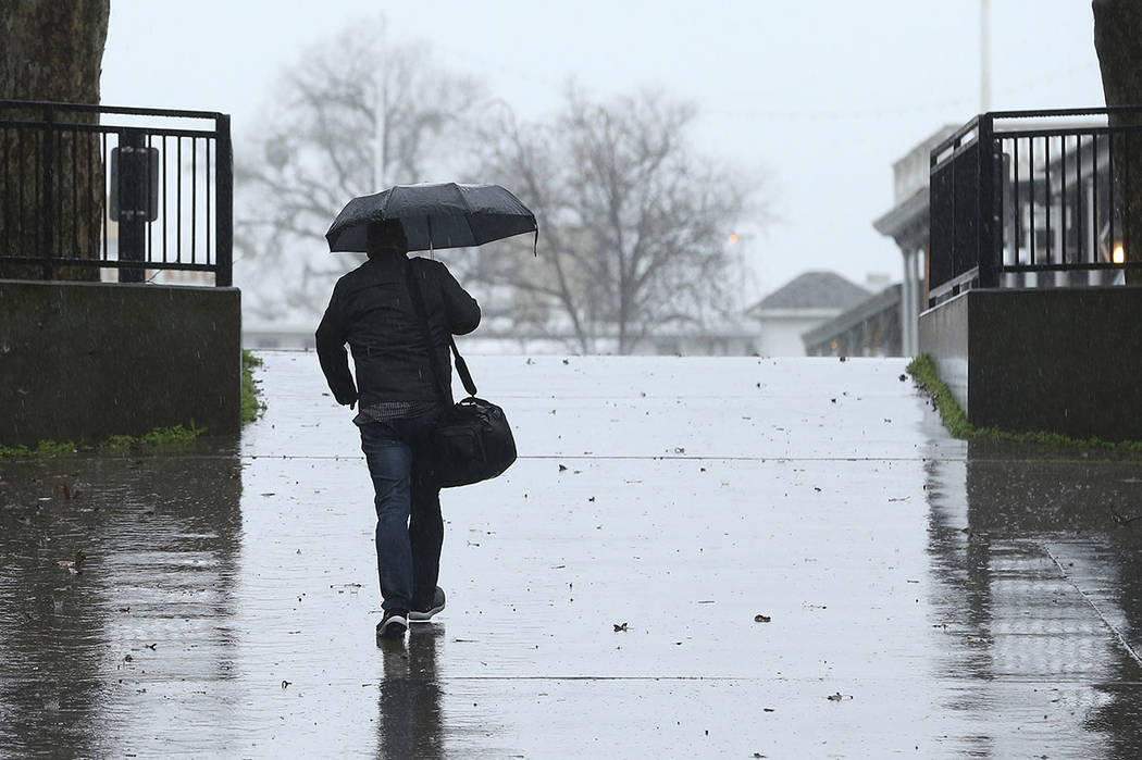 Umbrellas were put to use as a storm moved through Sacramento, Calif., Wednesday, Feb. 13, 2019. Rain is falling widely in Northern California and is expected to spread south.(AP Photo/Rich Pedron ...
