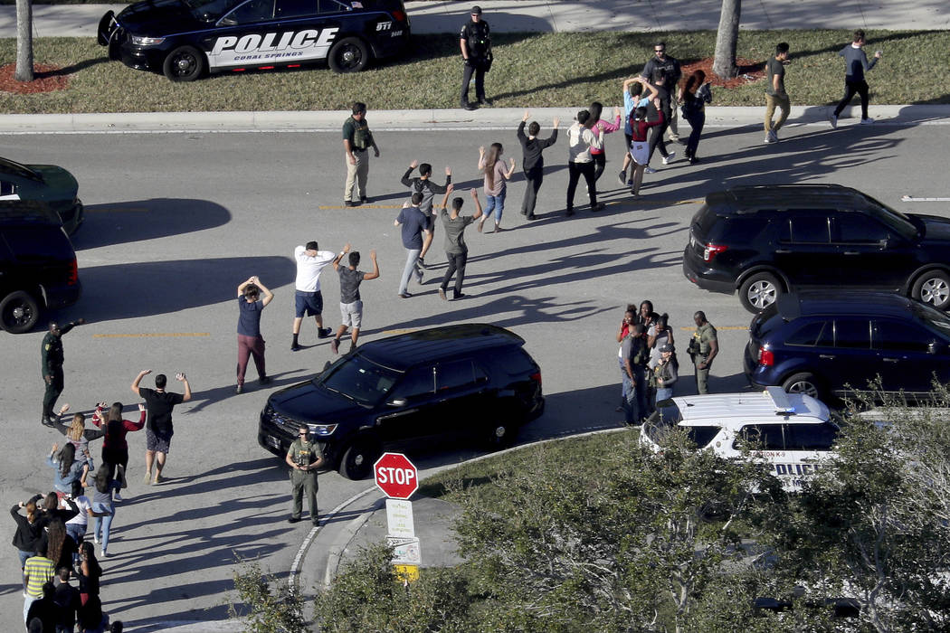 In this Wednesday, Feb. 14, 2018 file photo, students from Marjory Stoneman Douglas High School in Parkland, Fla., hold their hands in the air as they are evacuated by police after a shooter opene ...