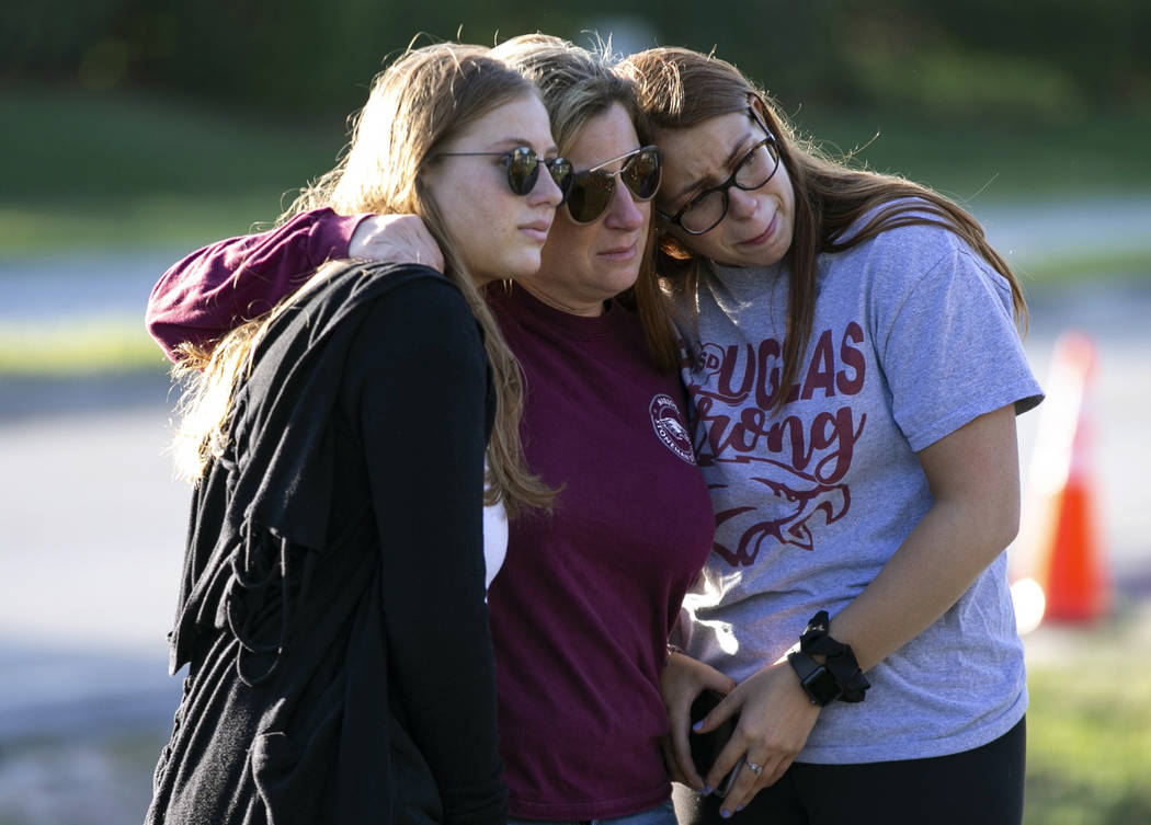 Emma Rothenberg, left to right, with her mother Cheryl Rothenberg and sister, Marjory Stoneman Douglas High School student Sophia Rothenberg embrace at a memorial marking the one-year anniversary ...