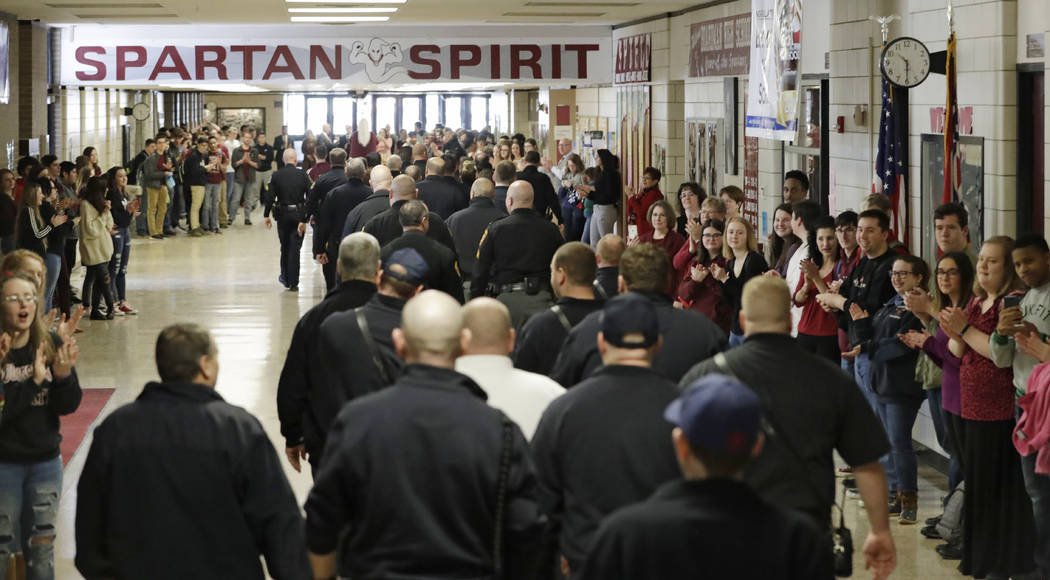 Students clap for first responders as they walk the hallway at Boardman High School after a lockdown drill, Thursday, Feb. 14, 2019, in Boardman, Ohio. Some students around the country marked the ...