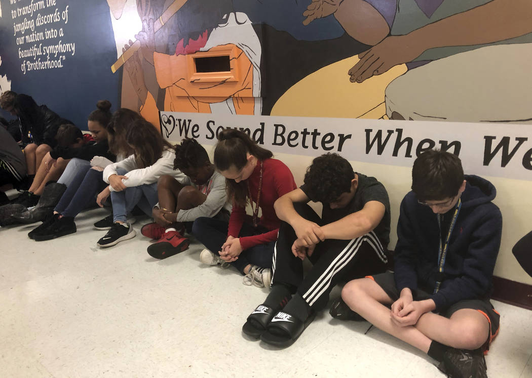 Students at Seminole Middle School in Plantation, Fla., participate in a moment of silence Thursday, Feb. 14, 2019, for the 14 students and three staff members killed one year ago at nearby Marjor ...