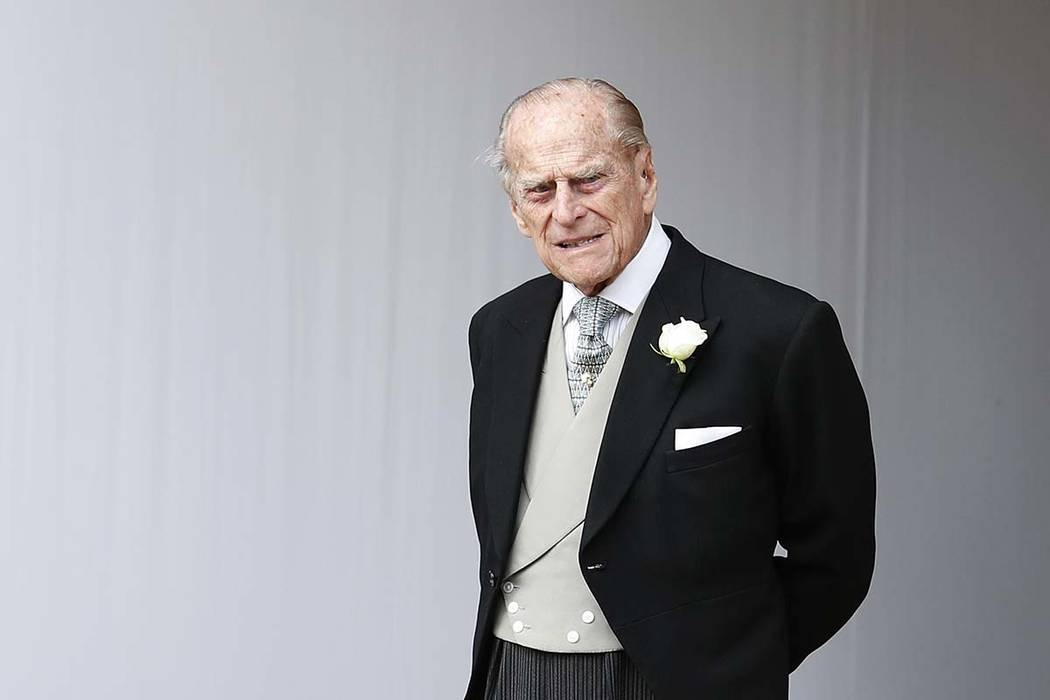 In this Friday, Oct. 12, 2018 file photo, Prince Philip waits for the bridal procession following the wedding of Princess Eugenie of York and Jack Brooksbank in St George's Chapel, Windsor Castle, ...