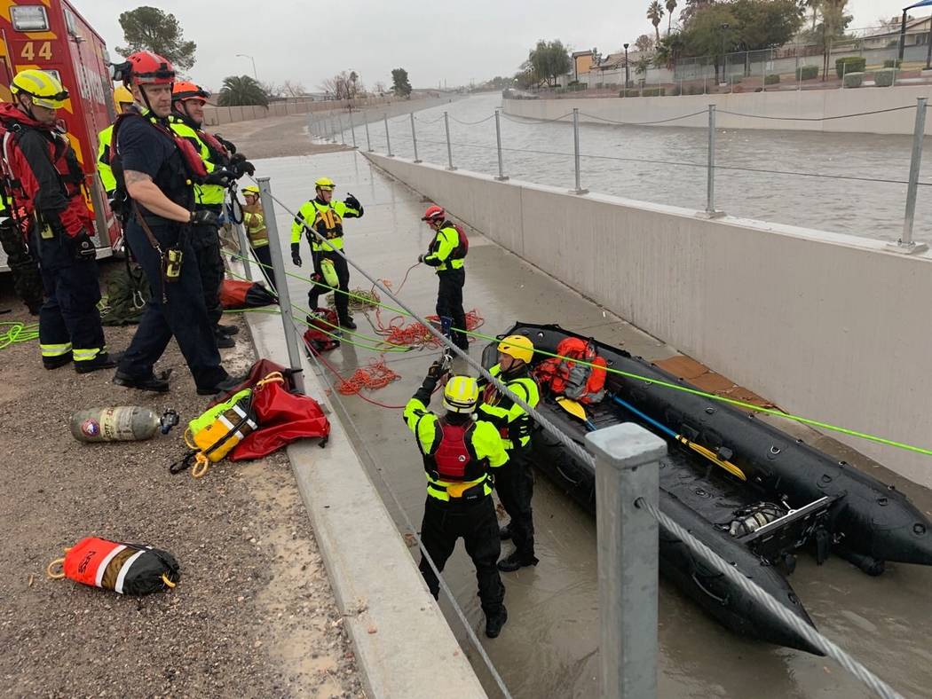 The North Las Vegas and Las Vegas firefighters gather after rescuing four people who were trapped underneath a bridge in the flooded Las Vegas Wash, near East Carey Avenue in North Las Vegas, on T ...