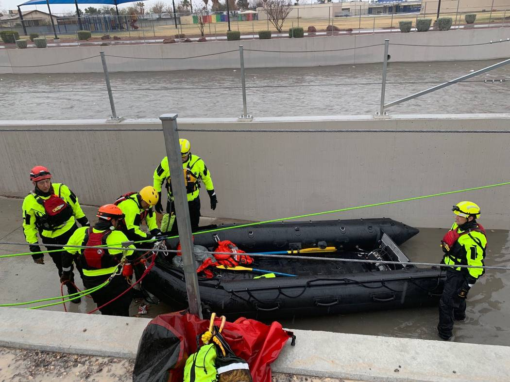 The North Las Vegas and Las Vegas firefighters rescued four people who were trapped underneath a bridge in the flooded Las Vegas Wash, near East Carey Avenue in North Las Vegas, on Thursday, Feb. ...