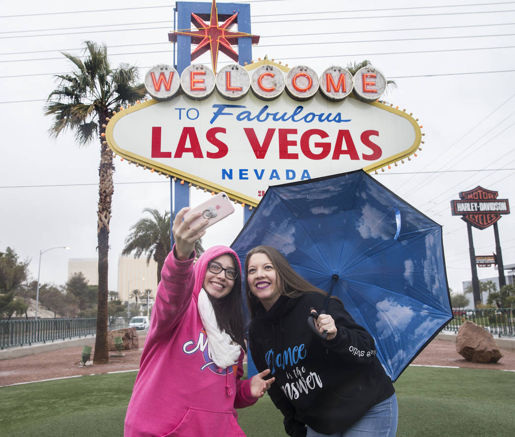 "Heavy rain doesn't stop Estefania Vazquez, left, and Valeria Vazquez, from Escondido, Calif., from taking selfies in front of the ""Welcome to Fabulous Las Vegas"" sign on Thursday, Feb. 1 ..."