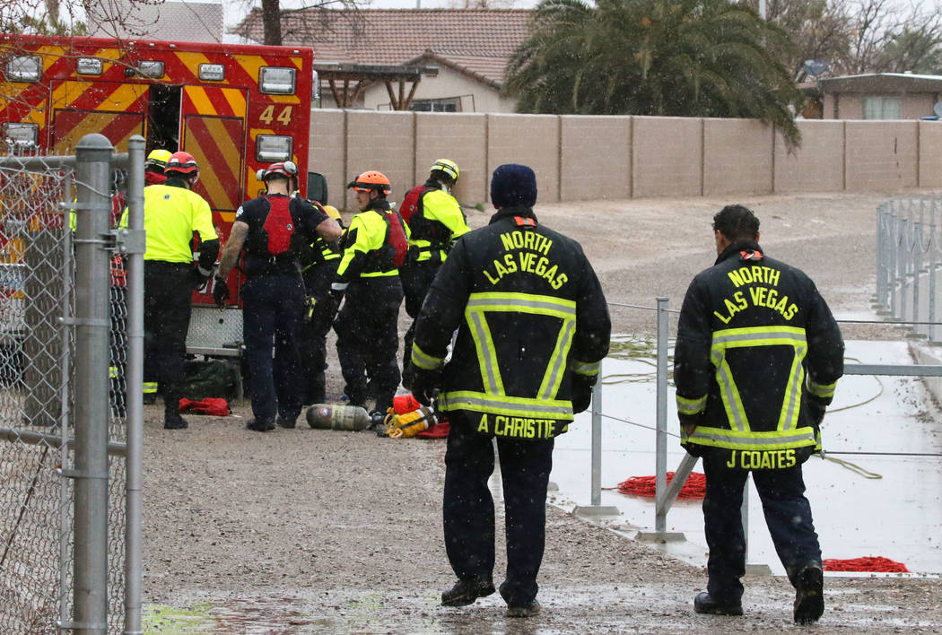 The North Las Vegas and Las Vegas firefighters are seen after rescuing a person who was trapped underneath a bridge in the flooded Las Vegas Wash, near East Carey Avenue on Thursday, Feb. 14, 2019 ...