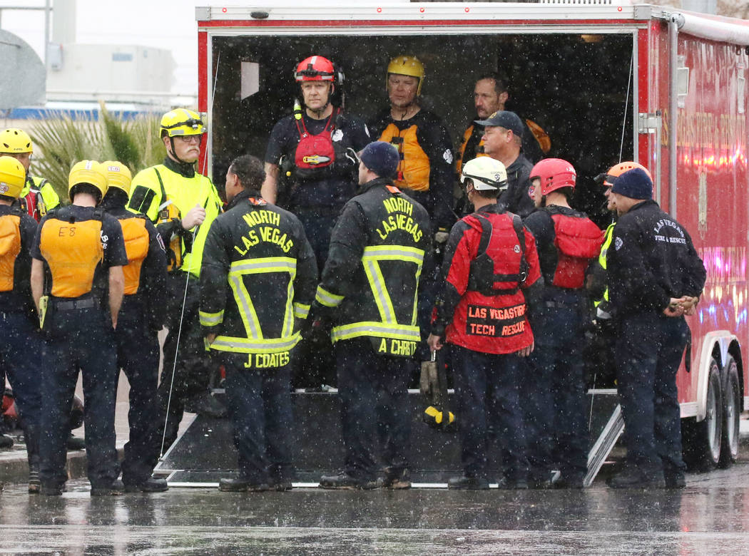 The North Las Vegas and Las Vegas firefighters gather after rescuing a person who was trapped underneath a bridge in the flooded Las Vegas Wash, near East Carey Avenue on Thursday, Feb. 14, 2019, ...
