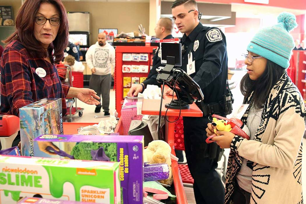 "Emelin Bautista, right, 10, checks out after shopping with North Las Vegas police officer Spencer Kinney during the annual ''Shop with a Cop"" event at Target at 7090 N. Fifth St. in North Las Vega ..."