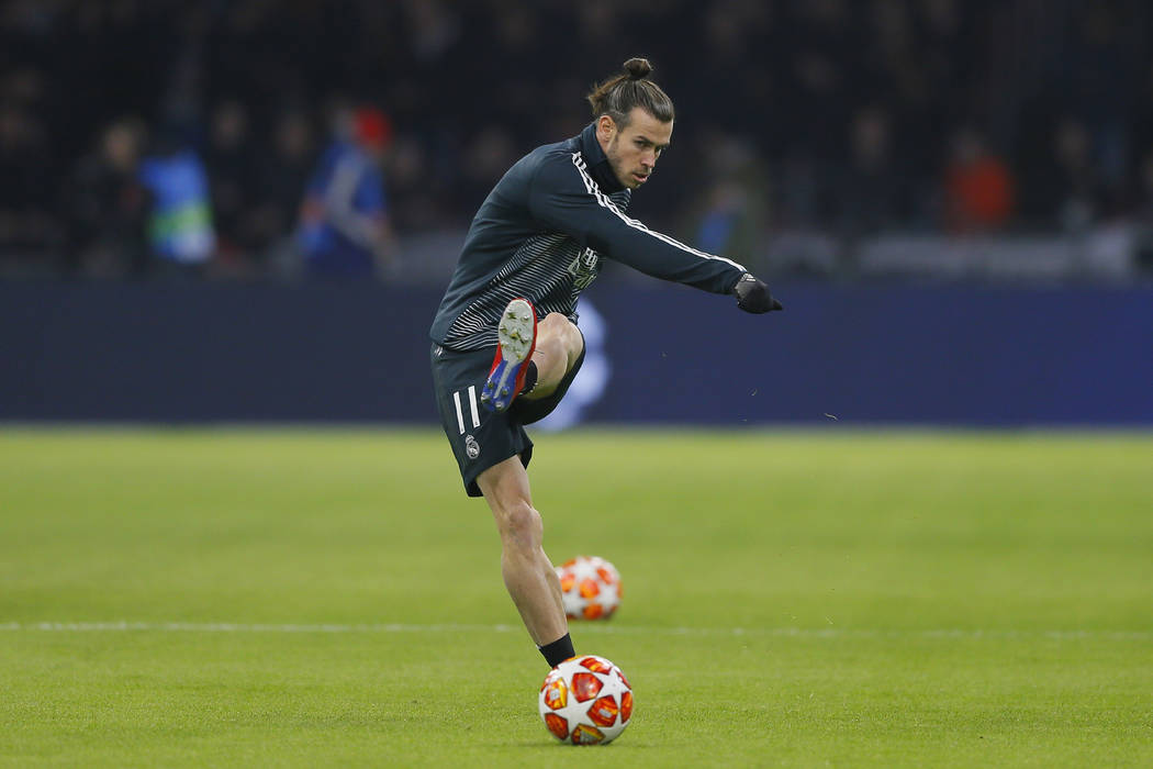 Real midfielder Gareth Bale shoots the ball as warming up during the first leg, round of sixteen, Champions League soccer match between Ajax and Real Madrid at the Johan Cruyff ArenA in Amsterdam, ...
