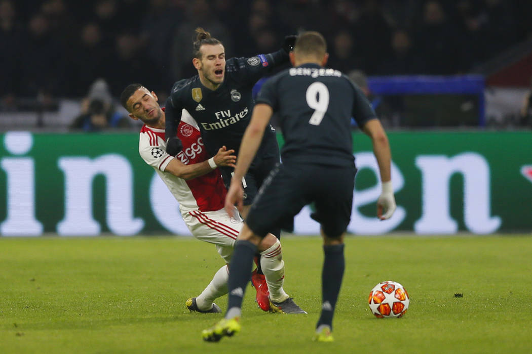 Real midfielder Gareth Bale, center, is tackled by Ajax's Hakim Ziyech, left, during the first leg, round of sixteen, Champions League soccer match between Ajax and Real Madrid at the Johan Cruyff ...