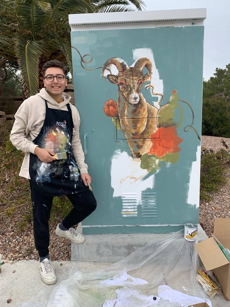 Alejandro Ponce stands next to the mural he painted on a utility box in Sun City Summerlin. Quails sit on both sides of the box while a bighorn sheep covers the front. (Courtesy)