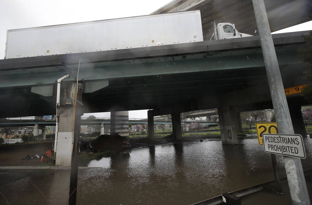 A truck drives over a flooded freeway underpass in San Francisco, Thursday, Feb. 14, 2019. The National Weather Service says the atmospheric river sagged southward from Northern California overnig ...