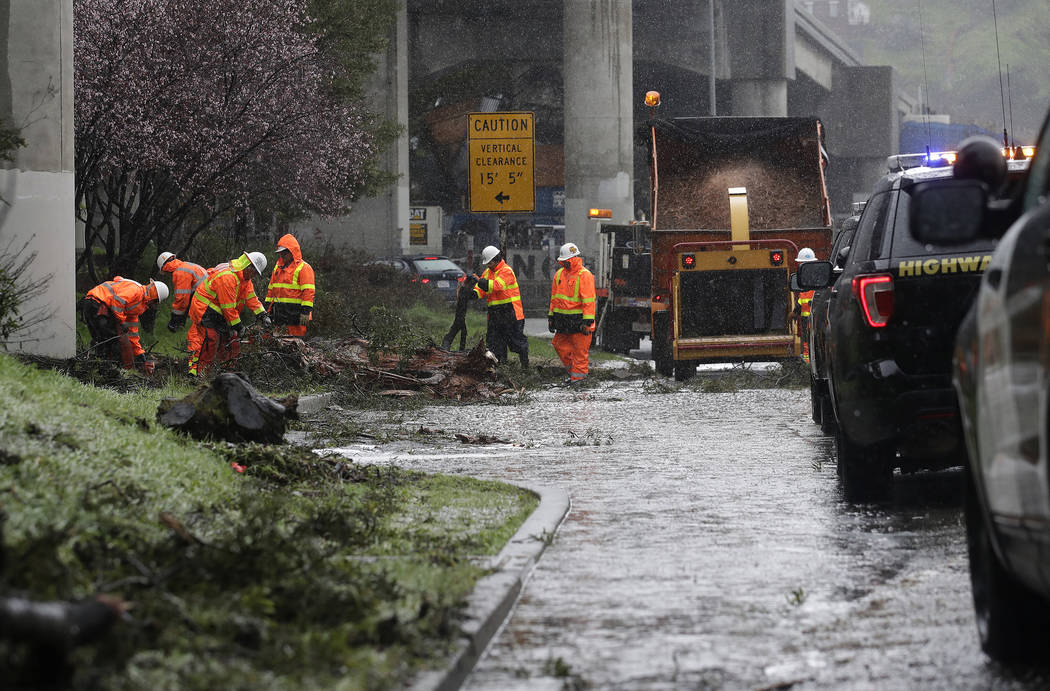 A Caltrans work crew removes debris near a flooded lane from under a freeway in San Francisco, Thursday, Feb. 14, 2019. The National Weather Service says the atmospheric river sagged southward fro ...
