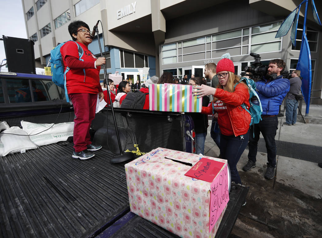 Marial Villanueva, left, a teacher at College View Elementary School, stands in the bed of a pickup truck as fellow teachers load up boxes of Valentine's Day cards destined for school administrato ...