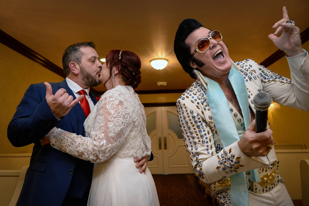 After 35 years together, Hugo and Sally Knight from Ireland kiss during their wedding ceremony as Elvis Presley impersonator Brendan Paul sings at Graceland Wedding Chapel in Las Vegas, Thursday, ...