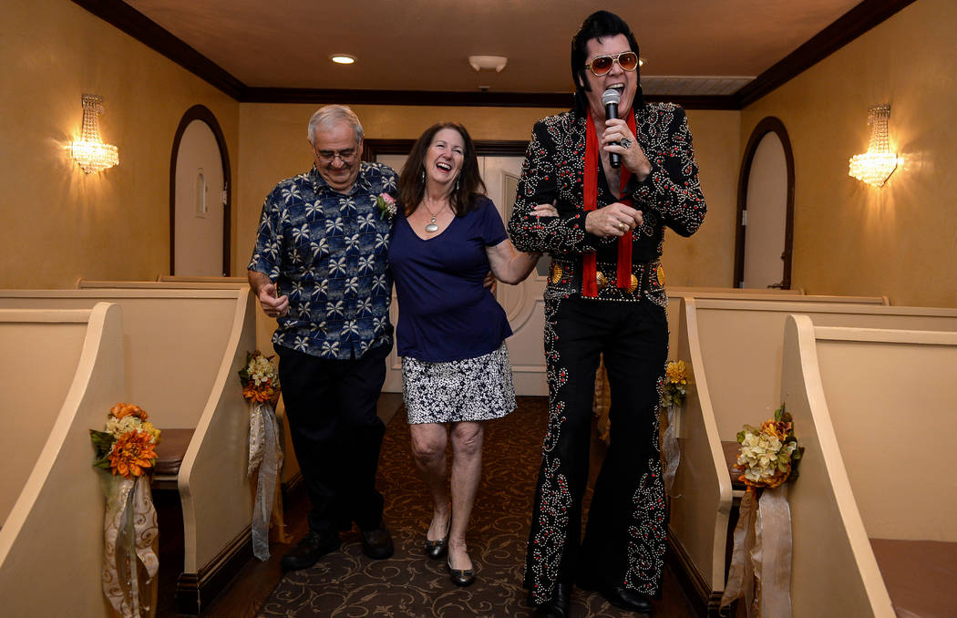 Robert Angellotti and Katherine Preble walk down the aisle with Elvis Presley impersonator Brendan Paul as he signs during their unofficial wedding ceremony at Graceland Wedding Chapel in Las Vega ...