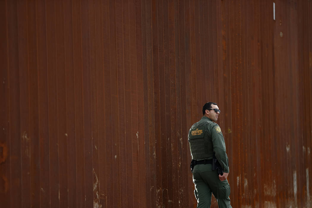 A U.S. Border Patrol agent walks in front of a section of newly-replaced border wall in San Diego on FILE - In this Jan 15, 2019. President Donald Trump would be taking an extraordinary step by de ...