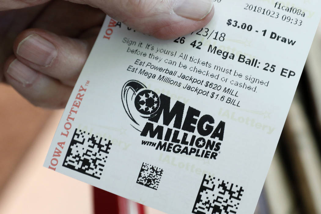A customer shows his Mega Millions lottery ticket at a local grocery store, Tuesday, Oct. 23, 2018. (AP Photo/Charlie Neibergall)