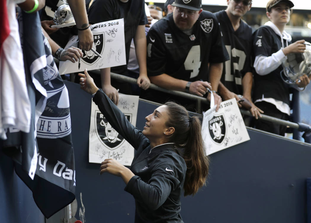 Kelsey Martinez, the Oakland Raiders' strength and conditioning assistant coach, signs autographs before an NFL football preseason game against the Seattle Seahawks, Thursday, Aug. 30, 2018, in Se ...